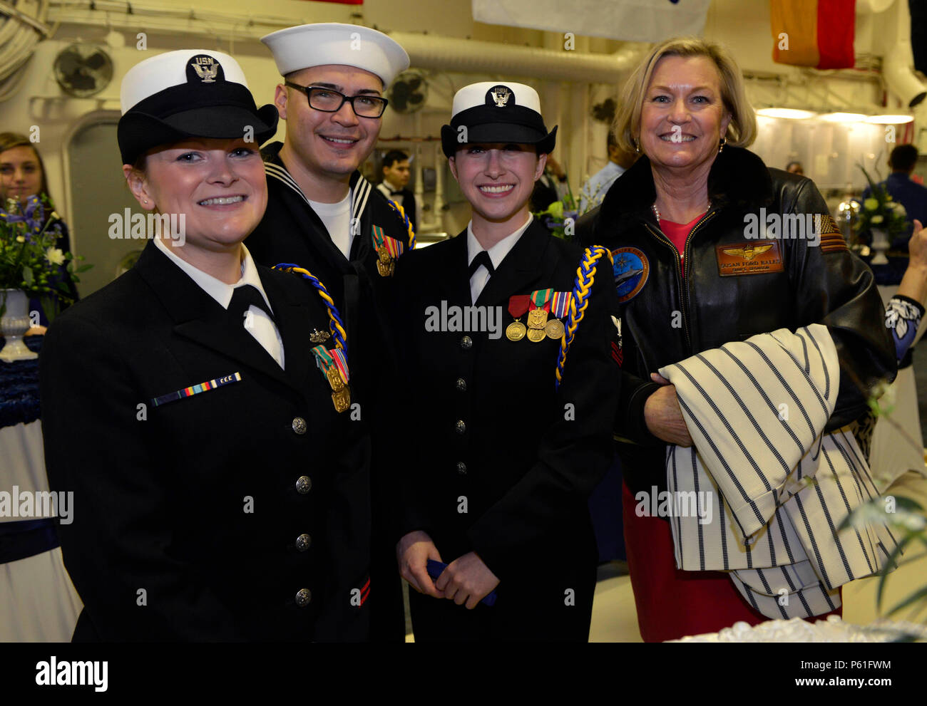 NEWPORT NEWS, Va., (April 8, 2016) – Ship Sponsor Susan Ford Bales poses with the Pre-Commissioning Unit Gerald R. Ford (CVN 78) choir during a reception following a change of command in the ship's hangar bay. Ford is the first of a new class of aircraft carriers currently under construction by Huntington Ingalls Newport News Shipbuilding. (U.S. Navy photo by Mass Communication Specialist Seaman Apprentice Gitte Schirrmacher/Released) - Stock Image