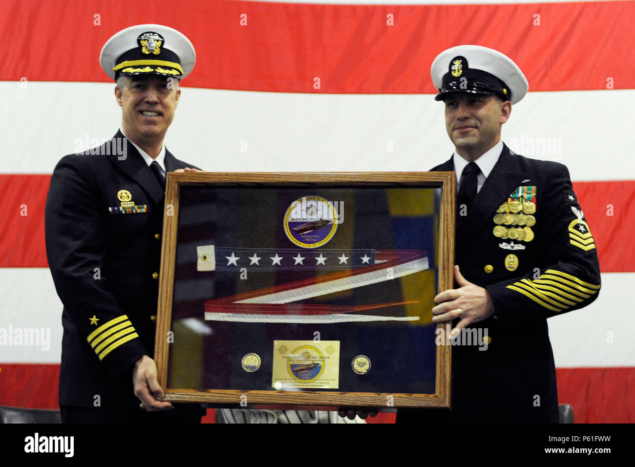 NEWPORT NEWS, Va., (April 8, 2016) Capt. John F. Meier is presented with the ship's pennant during a change of command ceremony in Pre-Commissioning Unit Gerald R. Ford's (CVN 78) hangar bay.  Ford is the first of a new class of aircraft carriers currently under construction by Huntington Ingalls Newport News Shipbuilding. (U.S. Navy photo by Mass Communication Specialist Seaman Cathrine Mae O. Campbell/Released) - Stock Image