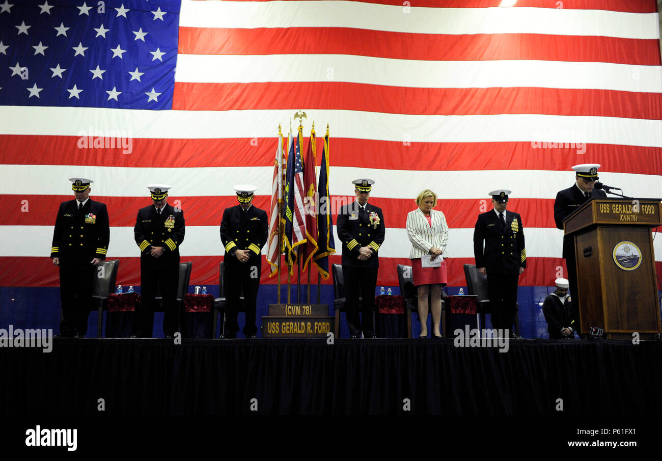 NEWPORT NEWS, Va., (April 8, 2016) The official party bow their heads for the benediction during a change of command ceremony in Pre-Commissioning Unit Gerald R. Ford's (CVN 78) hangar bay.  Ford is the first of a new class of aircraft carriers currently under construction by Huntington Ingalls Newport News Shipbuilding. (U.S. Navy photo by Mass Communication Specialist Seaman Cathrine Mae O. Campbell/Released) - Stock Image