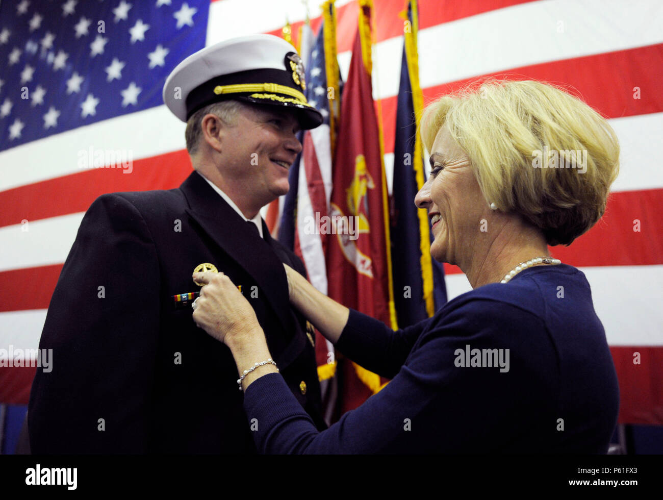 NEWPORT NEWS, Va., (April 8, 2016) Peggy McCormack, Capt. Richard McCormack's wife, moves his command-at-sea device from the left side of his jacket to the right signifying he has assumed command of Pre-Commissioning Unit Gerald R. Ford (CVN 78).  Ford is the first of a new class of aircraft carriers currently under construction by Huntington Ingalls Newport News Shipbuilding. (U.S. Navy photo by Mass Communication Specialist Seaman Cathrine Mae O. Campbell/Released) - Stock Image