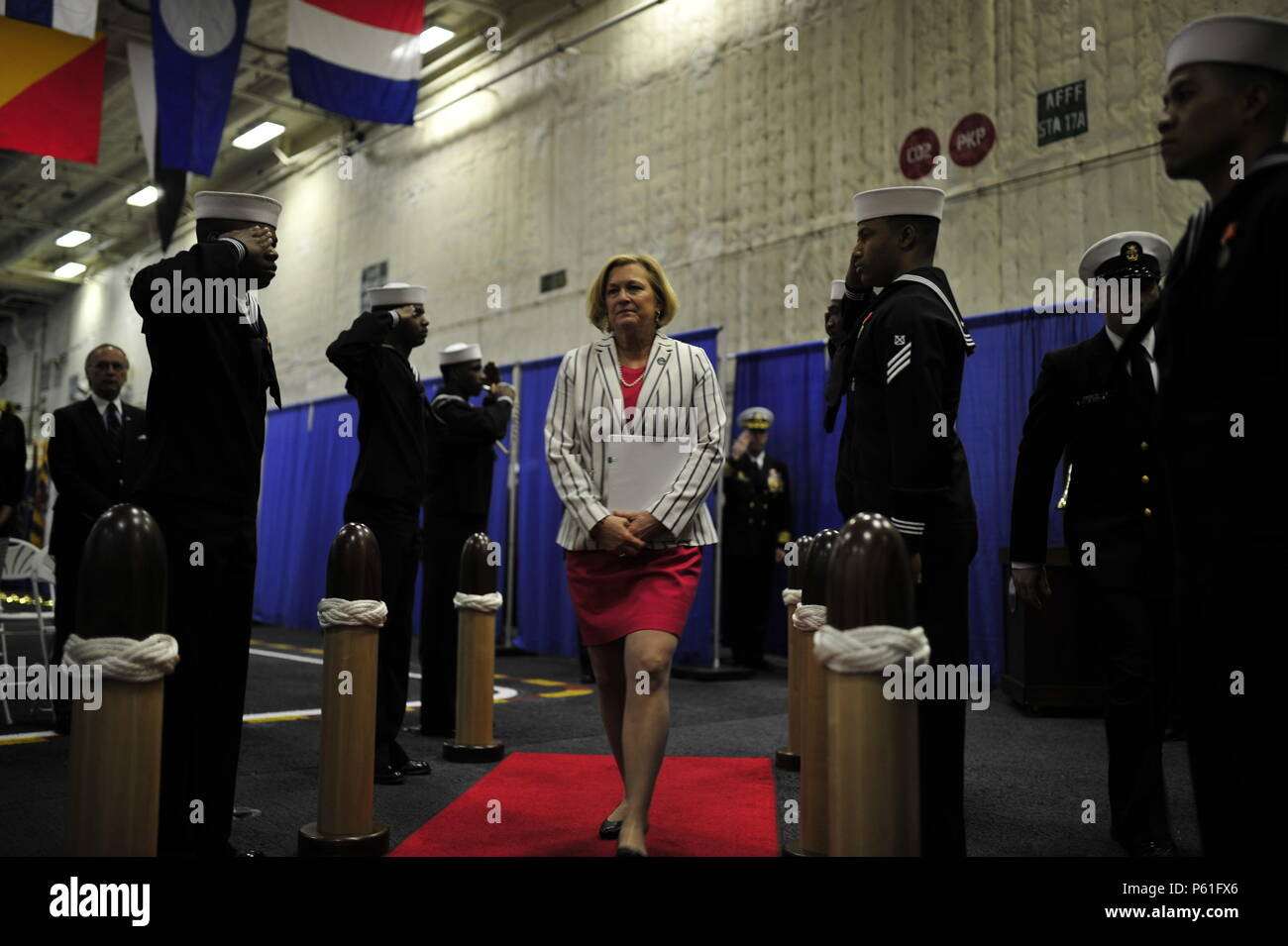 NEWPORT NEWS, Va., (April 8, 2016) Susan Ford Bales, ship sponsor and guest speaker, is rung aboard Pre-Commissioning Unit Gerald R. Ford (CVN 78) during a change of command in the hangar bay. Ford is the first of a new class of aircraft carriers currently under construction by Huntington Ingalls Newport News Shipbuilding. (U.S. Navy photo by Mass Communication Specialist Seaman Apprentice Connor D. Loessin/Released) - Stock Image