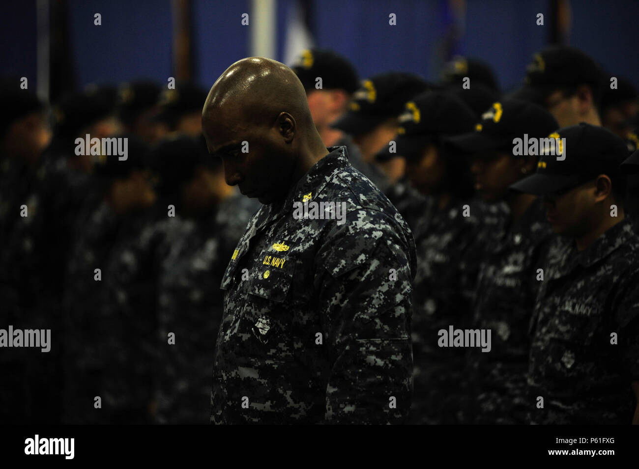 NEWPORT NEWS, Va., (April 8, 2016) Chief Warrant Officer Tony Cochran, the ship's boatswain, bows his head for the benediction during a change of command in Pre-Commissioning Unit Gerald R. Ford's (CVN 78) hangar bay. Ford is the first of a new class of aircraft carriers currently under construction by Huntington Ingalls Newport News Shipbuilding. (U.S. Navy photo by Mass Communication Specialist Seaman Apprentice Connor D. Loessin/Released) - Stock Image