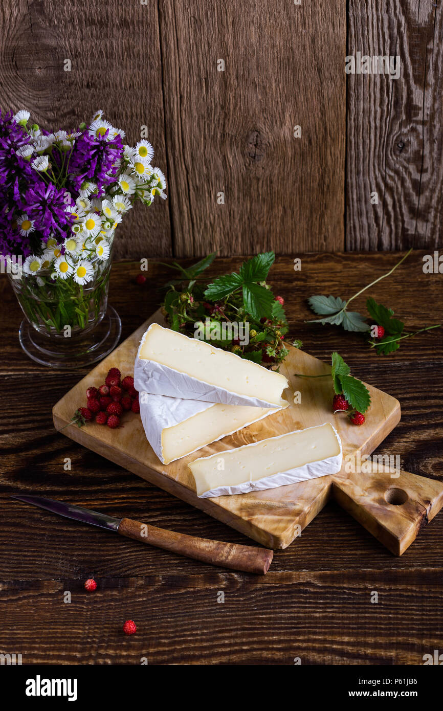 French brie cheese, wild strawberries and white purple wild flower bouquet on rural wooden table - Stock Image