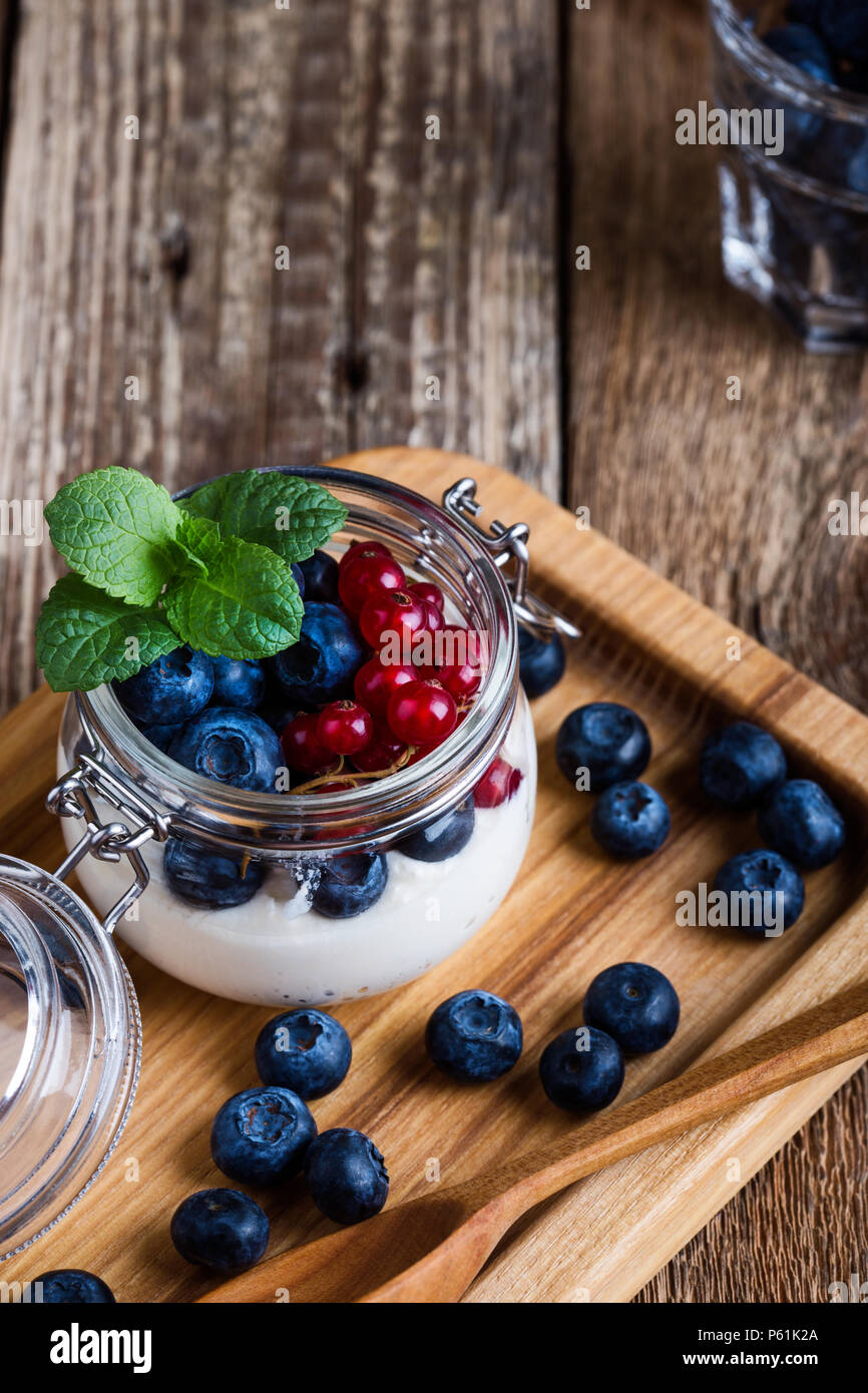 Cheesecake creme parfaits with blueberries and red currant berries served in jar, delicious summer no-bake dessert on rustic wooden table ready to eat - Stock Image