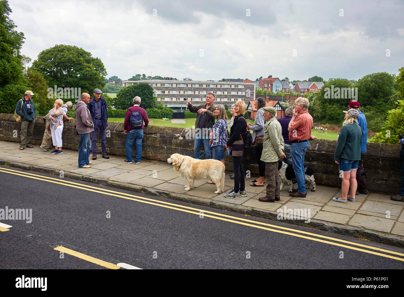 Steve Howe guides a party of visitors round the walls of Chester - Stock Image