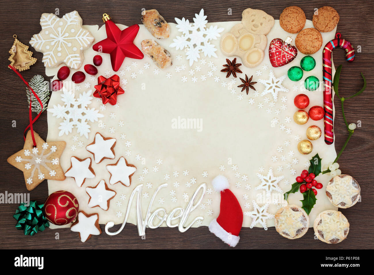 Noel and Christmas background border with silver sign and tree decorations, snowflakes, biscuits, cakes, chocolates and winter flora on parchment pape - Stock Image