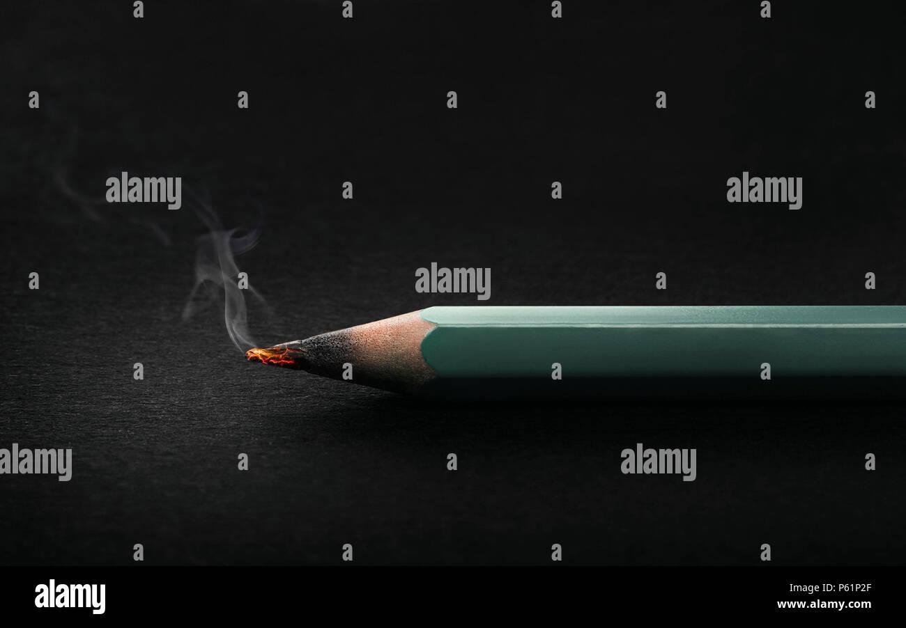 Pencil burning on dark background - Stock Image
