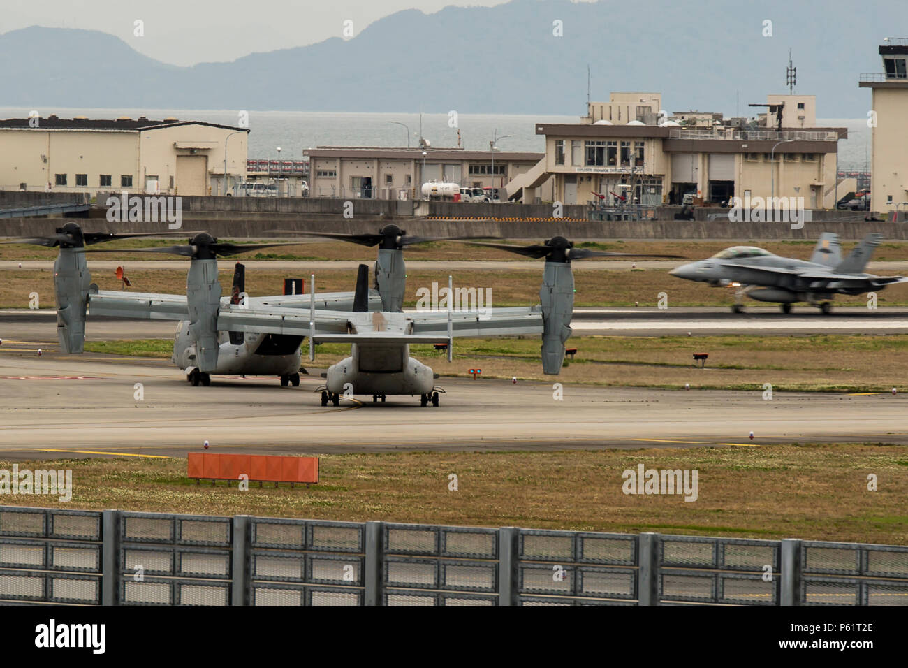 Two MV-22B Ospreys from Marine Medium Tiltrotor Squadron (VMM) 265 (Reinforced)  attached to the 31st Marine Expeditionary Unit wait to take off as an F/A-18 Hornet lands at Marine Corps Air Station Iwakuni, Japan, in support of the Government of Japan's relief efforts following the devastating earthquake near Kumamoto April 18, 2016. The long-standing relationship between Japan and the U.S. allows U.S. military forces in Japan to provide rapid, integrated support to the Japan Self-Defense Forces and civil relief efforts. (U.S. Marine Corps photo by Lance Cpl. Aaron Henson/Released) Stock Photo