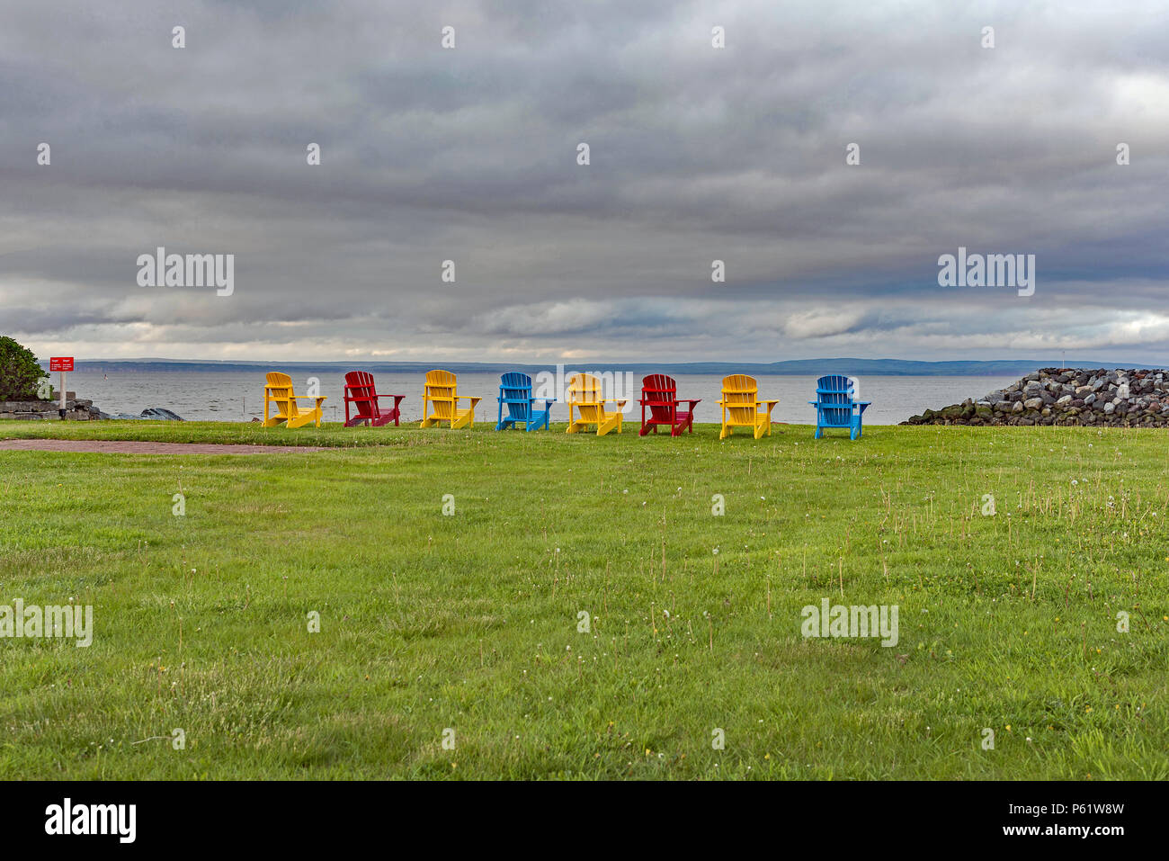 Colourful chairs overlooking the Bay of Fundy in Alma, New Brunswick, Canada. - Stock Image