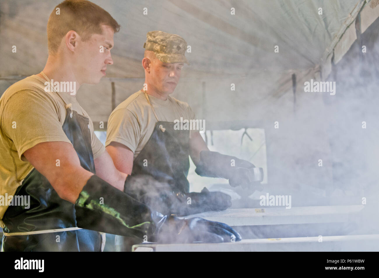 Spc. Maxim Trifonov, a motor transport operator with the 733rd Transportation Company, left, and Spc. Ezra Utting, also with the 733rd T.C., sanitize cooking utensils for the food services specialists competing in the annual Philip A. Connelly Award competition at Fort Indiantown Gap, Pa., April 23, 2016. (U.S. Army photo by Staff Sgt. Dalton Smith / Released) Stock Photo