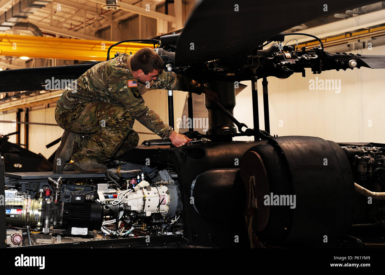 Missouri Army National Guard Staff Sgt. Keith Neiman, a crew chief assigned to the 1-135th Attack Reconnaissance Battalion Army Aviation Support Facility #1, performs routine maintenance on a UH-60 Black Hawk utility helicopter at Whiteman Air Force Base, Mo., April 1, 2016. More than 90 enlisted aircraft maintainers, who previously only worked on the AH-64 Apache, are in the process of certifying to perform maintenance on Black Hawks following the helicopter's recent arrival. - Stock Image