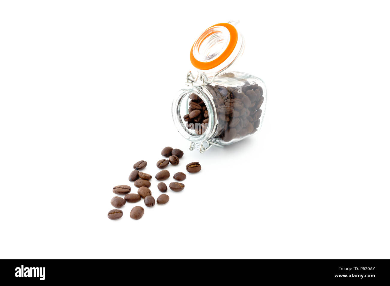 Square mini preserving jar filled with roasted coffee beans and coffee beans scattered on white background. - Stock Image