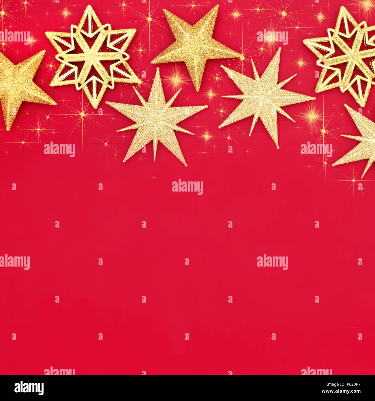 Christmas gold sparkling star bauble decorations with decorative stars  forming an abstract background on red with copy space. Traditional  Christmas gr