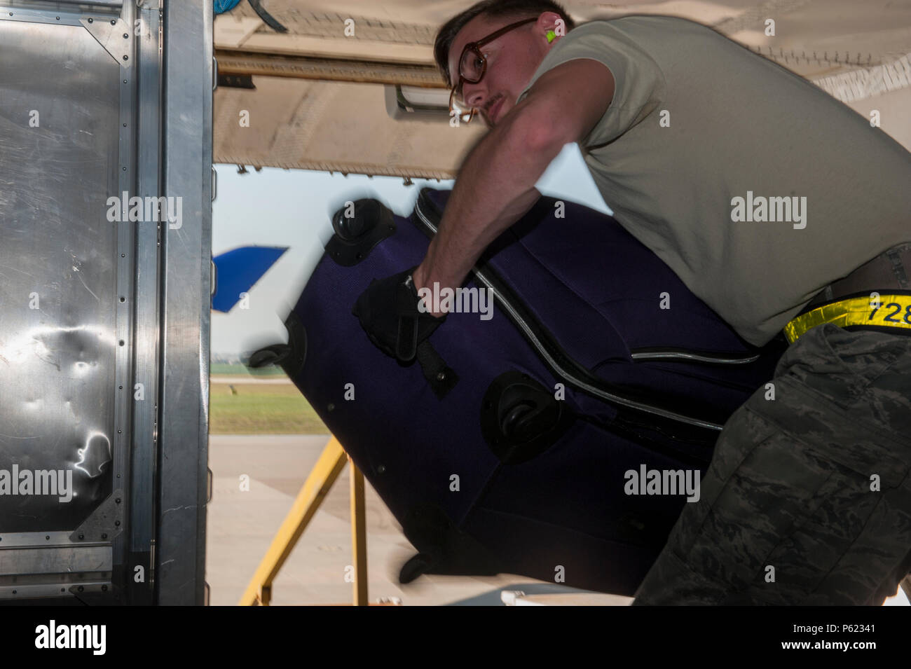 U.S. Air Force Senior Airman Chase Baker, 728th Air Mobility Squadron air terminal operations center information controller, throws luggage into the storage area of an Atlas Air 747 airliner April 1, 2016 at Incirlik Air Base, Turkey. Airmen from the 728th AMS built, staged, transported, and loaded luggage into aircraft to aid in the process of an ordered departure. (U.S. Air Force photo by Staff Sgt. Jack Sanders/Released) - Stock Image