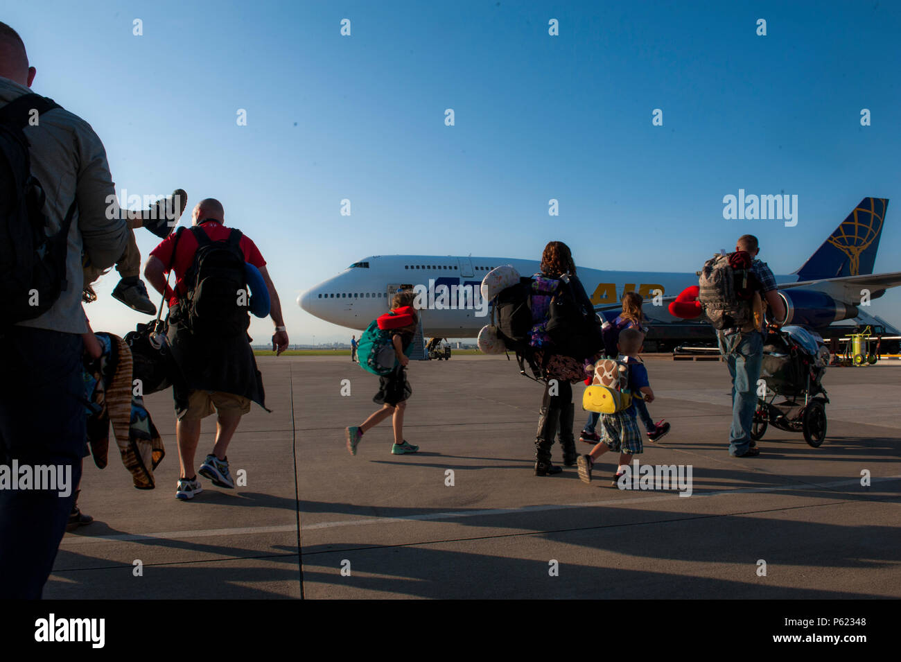 Families of U.S. Airmen and families of Department of Defense civilians walk toward an Atlas Air 747 airliner April 1, 2016 at Incirlik Air Base, Turkey. Department of Defense dependents were ordered to depart Incirlik AB March 29, 2016. (U.S. Air Force photo by Staff Sgt. Jack Sanders/Released) - Stock Image