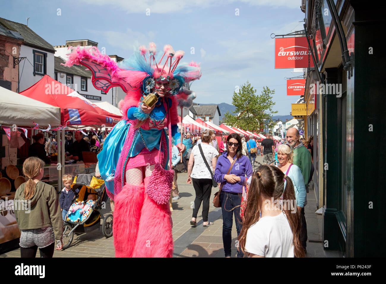 street entertainer entertaining children at Keswick market on main street Lake District Cumbria England UK - Stock Image