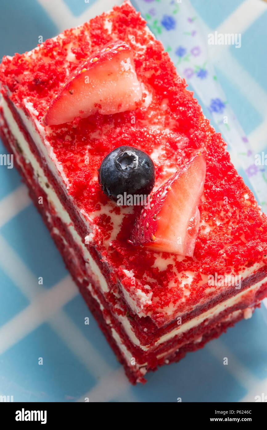 Red velvet cake with cream, strawberries and blueberry - Stock Image