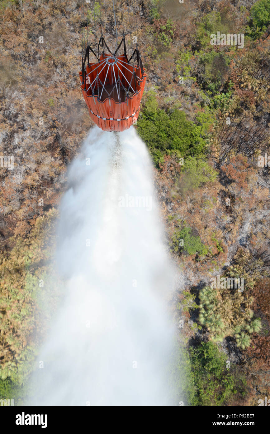 A U.S. Army CH-47 Chinook uses a Bambi Bucket to drop water on a fire April 1, 2016, near Tela, Honduras, at the request of Honduran President Juan Orlando Hernandez. The Chinooks were a part of aircraft from the 1-228th Aviation Regiment to support the Honduran Fire Department, Air Force and Army in the firefighting efforts. (U.S. Air Force photo by Staff Sgt. Westin Warburton/ Released) Stock Photo
