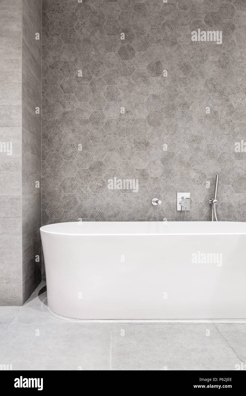 Modern bathroom with white bathtub and gray, hexagonal wall tiles ...