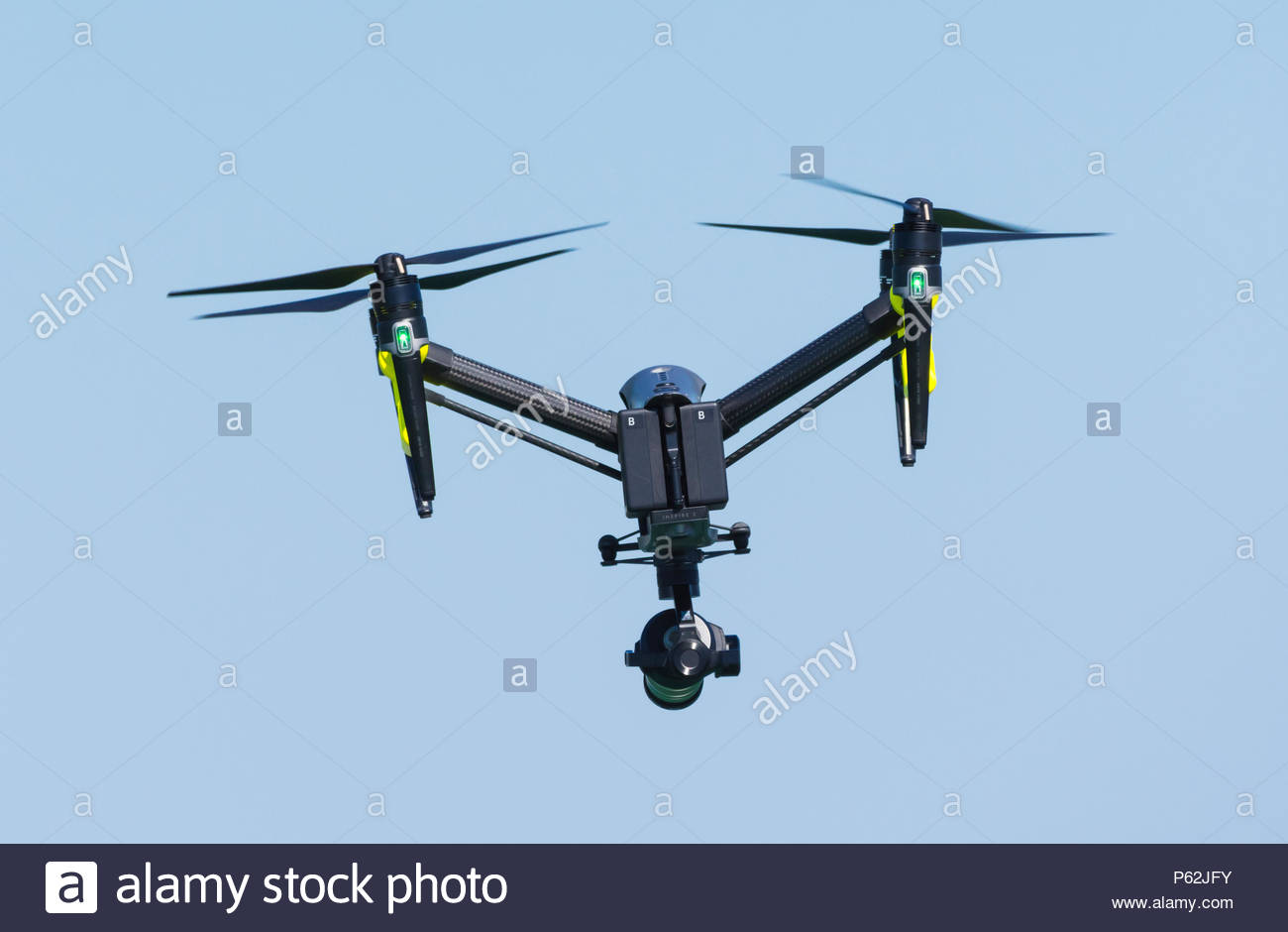 DJI Inspire 2 Quadcopter fitted with a video camera flying against blue sky in the UK. - Stock Image