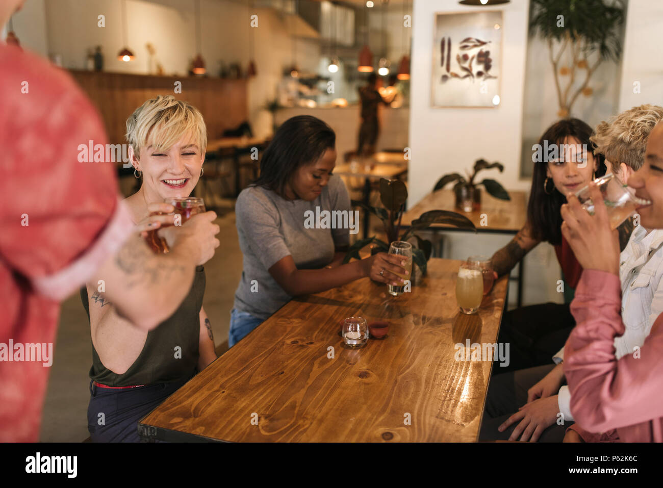 Group of smiling female friends ordering drinks in a bistro - Stock Image
