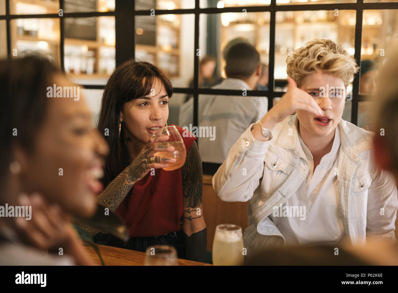 Diverse young girlfriends hanging out together in a trendy bistro - Stock Image