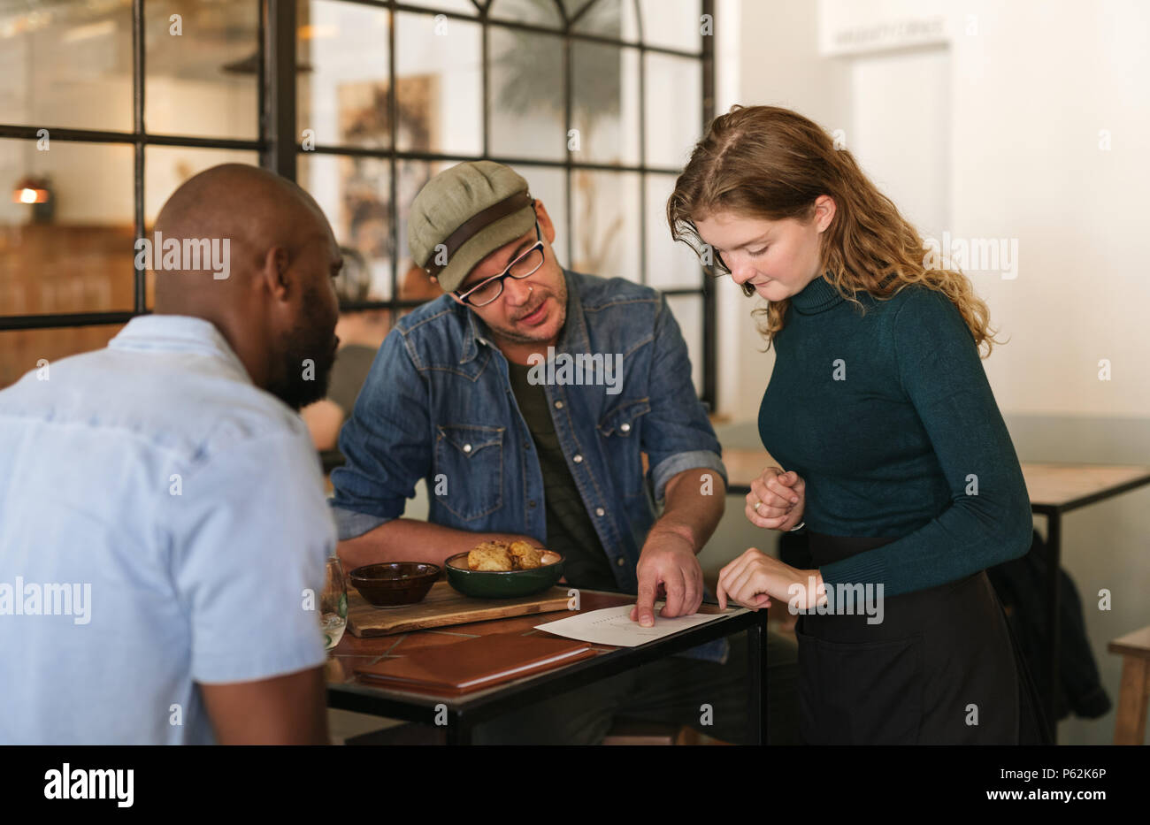 Waitress explaining the menu to customers in a bistro - Stock Image