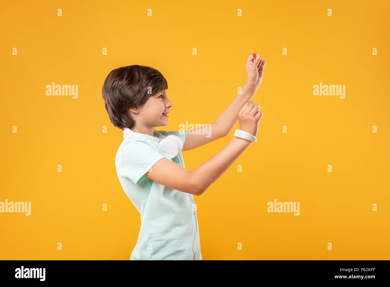 Happy preteen holding tiny flags - Stock Image