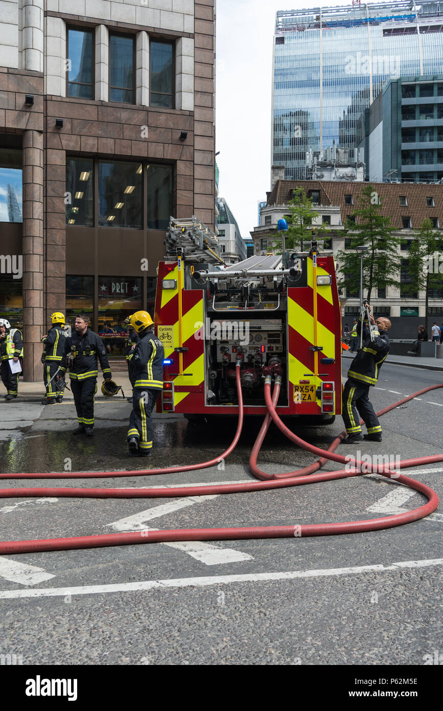 London Fire Brigade crews and fire tenders attend an emergency incident at St. Mary Axe and Undreshaft in the City of London - Stock Image
