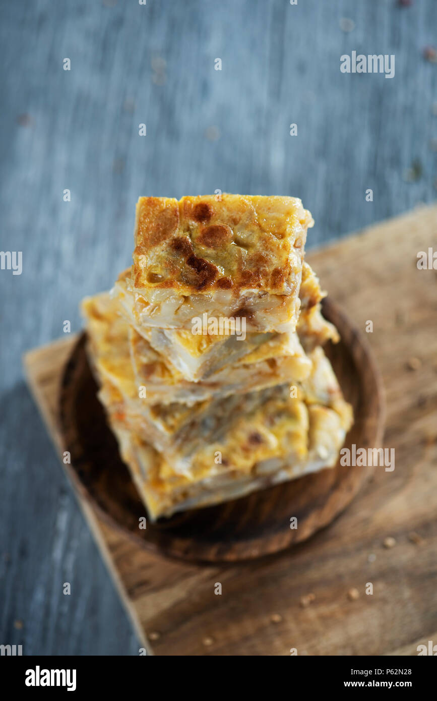 some pieces of typical tortilla de patatas, spanish omelet, on a wooden plate, placed on a gray rustic wooden table - Stock Image