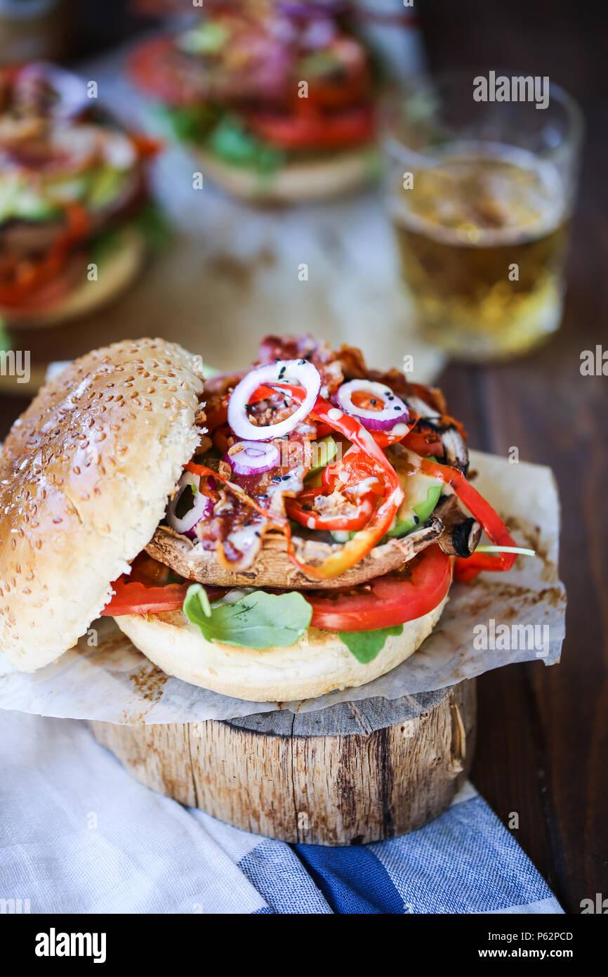Delicious grilled portobello mushroom burger with a lot of veggies - Stock Image
