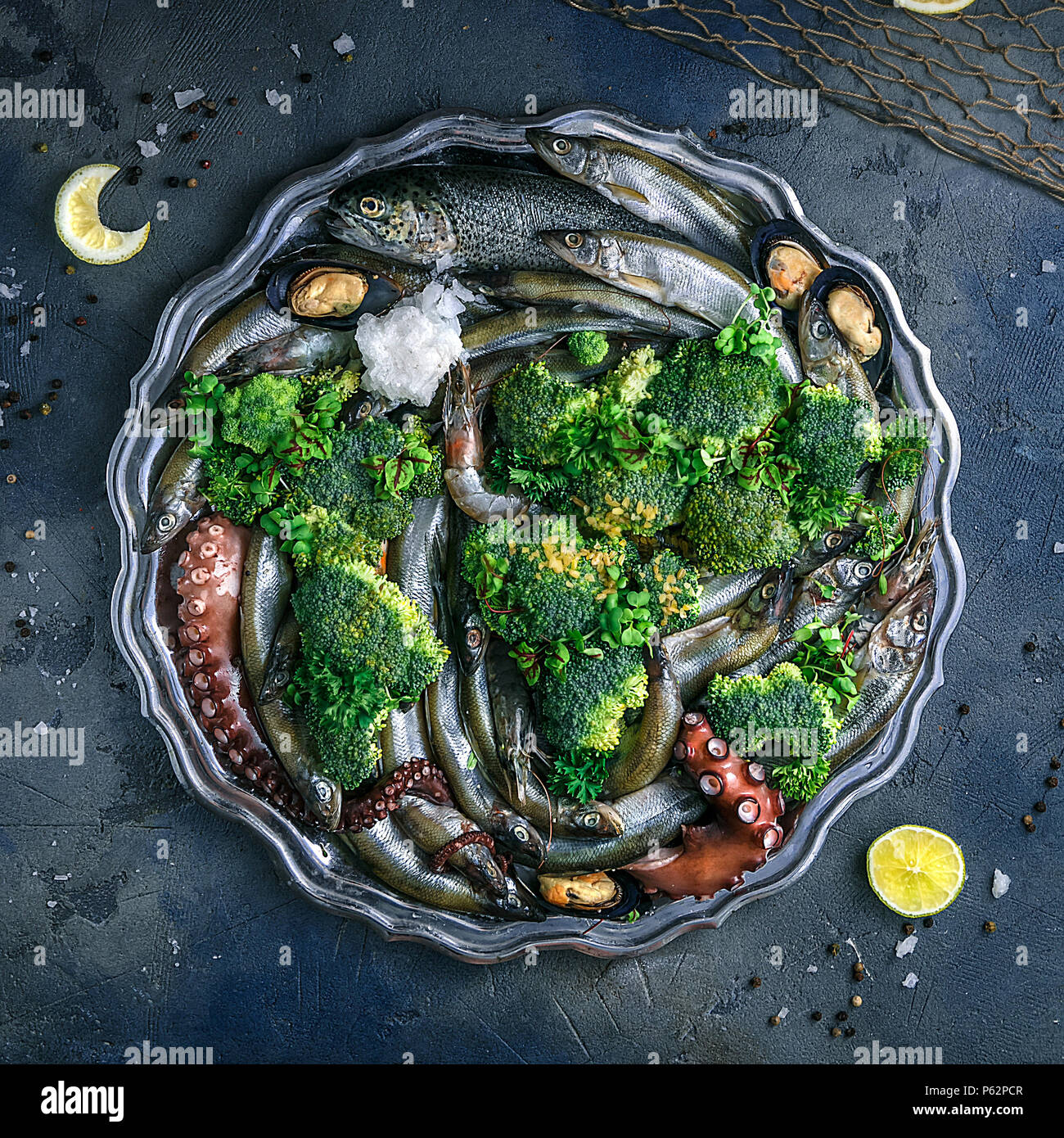 Variety of fresh seafood on a plate with green vegetables Stock Photo