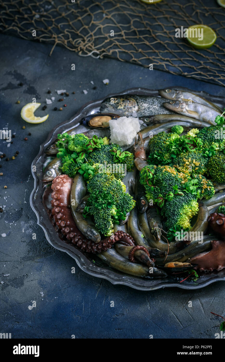 Raw Mixed seafood on a silver plate, dark background - Stock Image