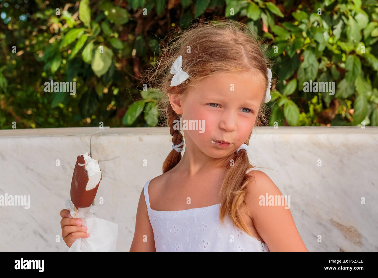 113912f40 Pretty little girl eating an ice cream outdoors.Portrait of funny ...