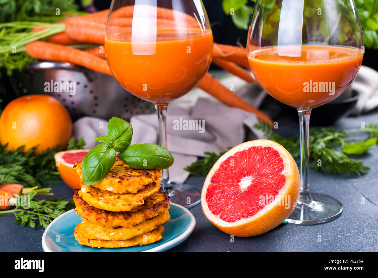 Juice from fresh carrots and grapefruit in a glass and fragrant pancakes for breakfast. vitamin drink for a healthy diet. Vitamins in food. Copy space - Stock Image