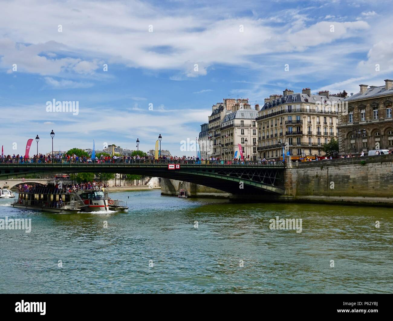 Tourist boat passing under a bridge where crowds of people are participating in an Olympic Day celebration, Paris, France Stock Photo