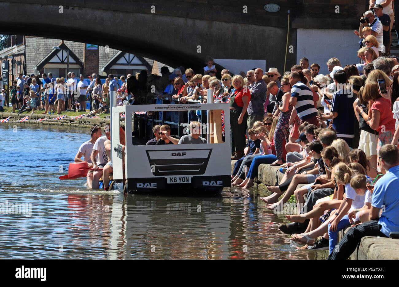 On a glorious summers Sunday the winning raft in the race along the Leeds and Liverpool canal has just crossed the line at Burscough Wharf - Stock Image