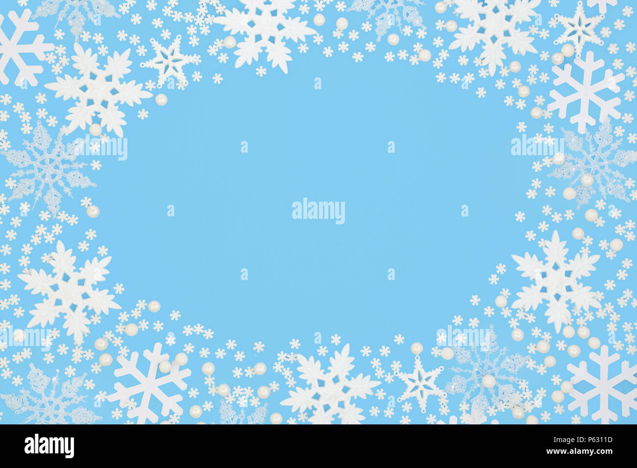 snowflake abstract background border on pastel blue background festive card for the christmas holiday and winter season