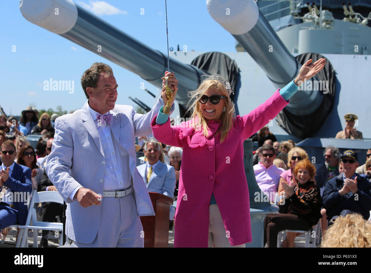 Anna Kooiman, Queen of the Azalea Festival, rejoices after cutting the ceremonial cake with the naval officer's sword, kick-starting the celebration of the 75th anniversary of the USS North Carolina (BB-52) Battleship's commissioning in Wilmington, N.C., April 9, 2016. Marines and sailors from 2nd Tank Battalion and other 2nd Marine Division units volunteered to work with museum staff and members of Living History to give real-life experiences to guests partaking in the festivity. (U.S. Marine Corps photo by LCpl. Miranda Faughn/Released) Stock Photo