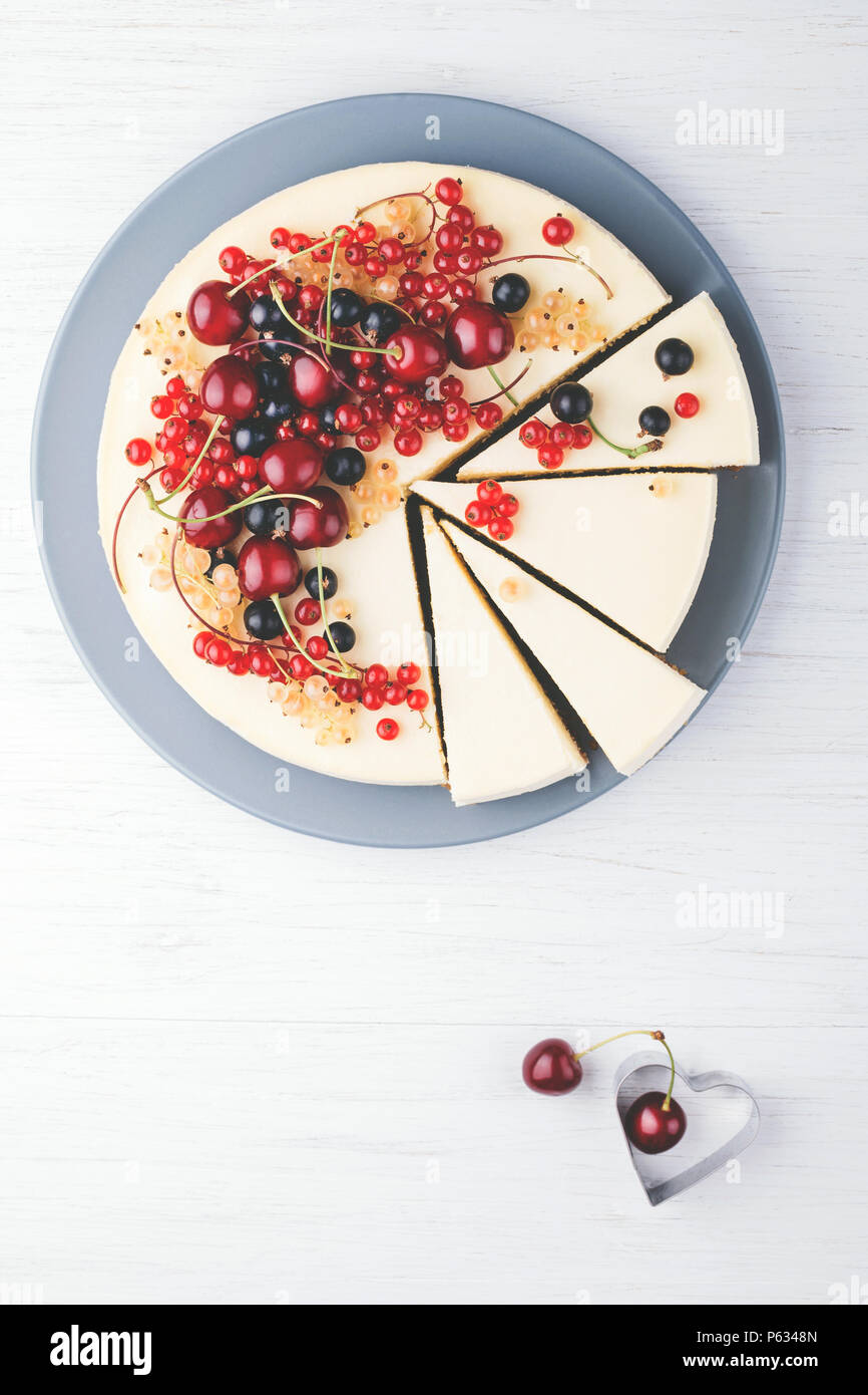 Homemade cheese cake New York with berries on white wooden table. Top view. Red currant, black currant and cherry. - Stock Image