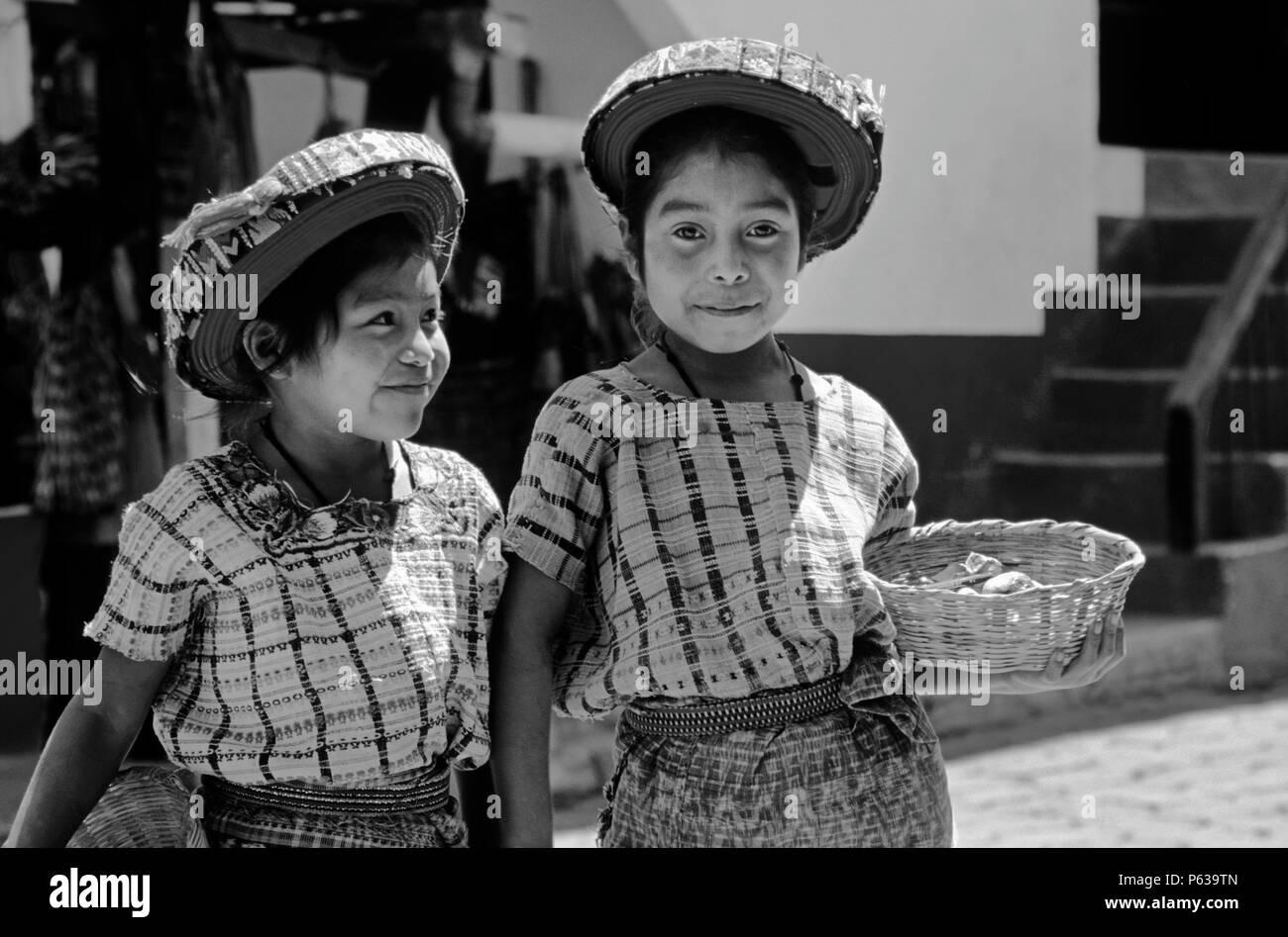 TZUTUJIL GIRLS in traditional handmade HUIPILS (blouses) and TOCAYALS (headresses) - SANTIAGO ATITLAN, GUATEMALA - Stock Image