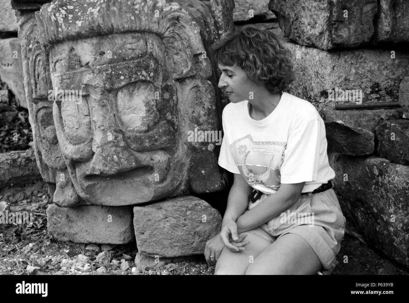 TOURIST with ancient MAYAN stone head, probably a god or ruler, found at the COPAN RUINS - HONDURAS - Stock Image