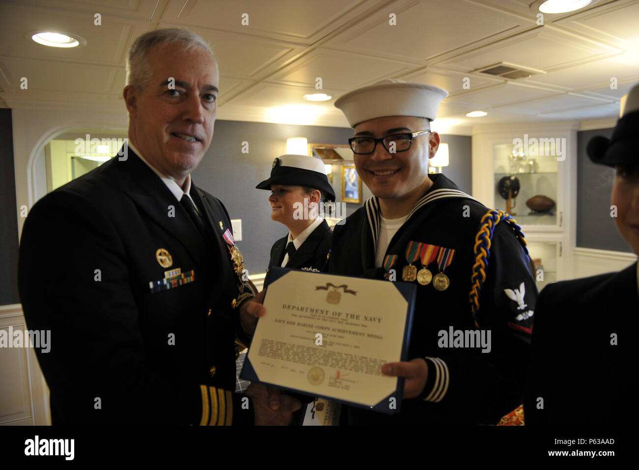 NEWPORT NEWS, Va., (April 8, 2016) A Pre-Commissioning Unit Gerald R. Ford (CVN 78) command choir Sailor receives a Navy and Marine Corps Achievement medal from the ship's Commanding Officer Capt. John F. Meier.  Ford is the first of a new class of aircraft carriers currently under construction by Huntington Ingalls Newport News Shipbuilding. (U.S. Navy photo by Mass Communication Specialist 3rd Class Matthew Fairchild/Released) - Stock Image