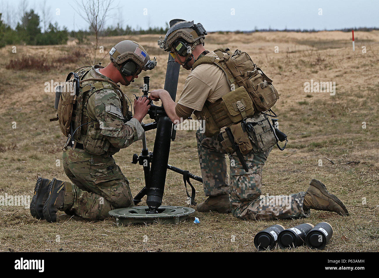 A Special Operations Command Forward Eastern Europe soldier shows a Latvian special forces soldier how to make adjustments before firing 81mm mortars during weapons familiarization training, April 13, at Adazi Military Base, Latvia. While in the area, SOC-FWD-EE soldiers have conducted weapons and medical training for various Army units supporting Operation Atlantic Resolve, a multinational demonstration of continued U.S. commitment to the collective security of North Atlantic Treaty Organization allies.(U.S. Army photo by Sgt. Paige Behringer, 10th Press Camp Headquarters) - Stock Image
