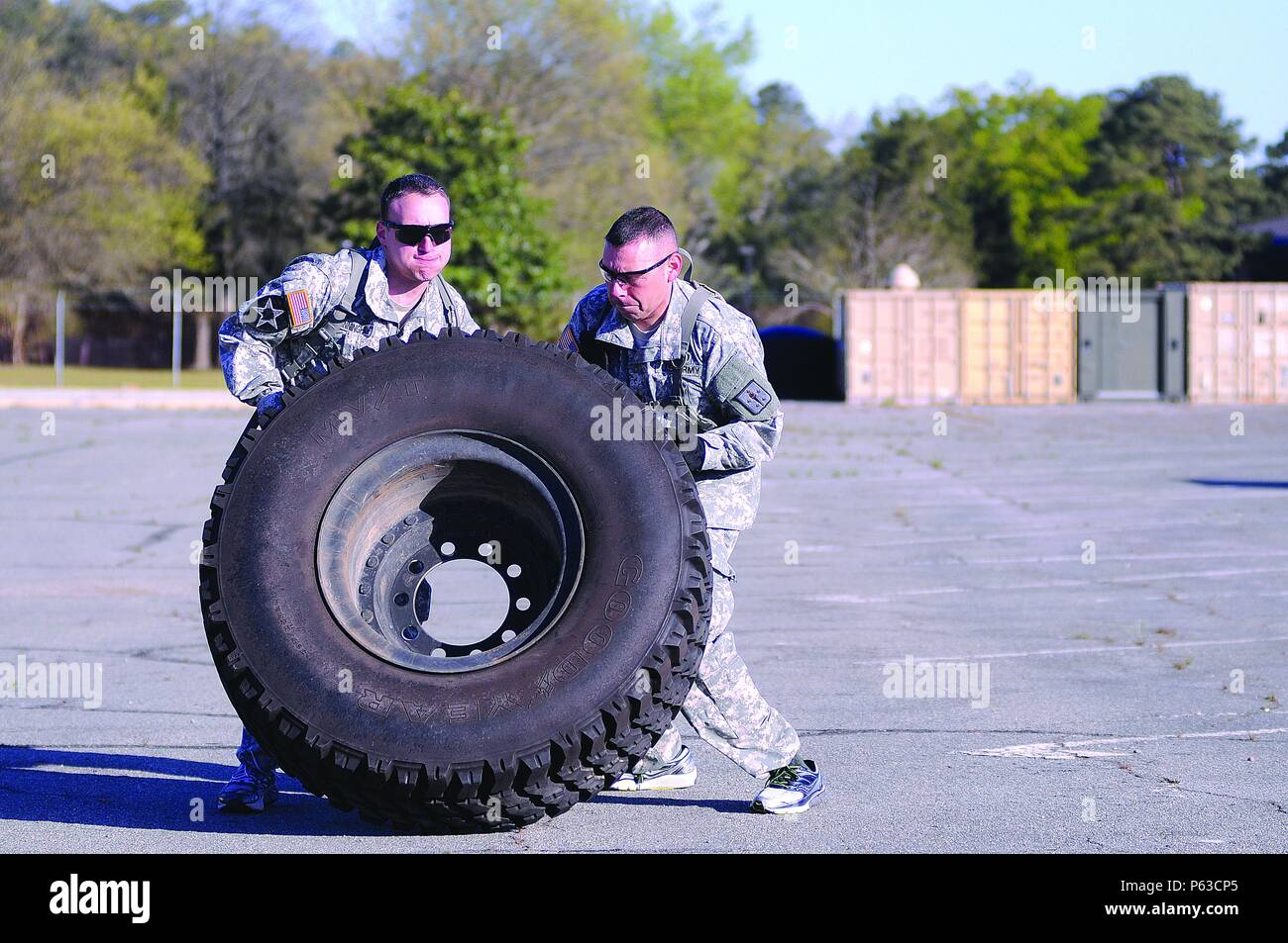 First Lt. Shaun Cunningham and Staff Sgt. Jesus Campos expend much energy in flipping a tire for some distance during the Ordnance Amazing Race April 16 at the CASCOM Consolidated Motor Pool. Stock Photo