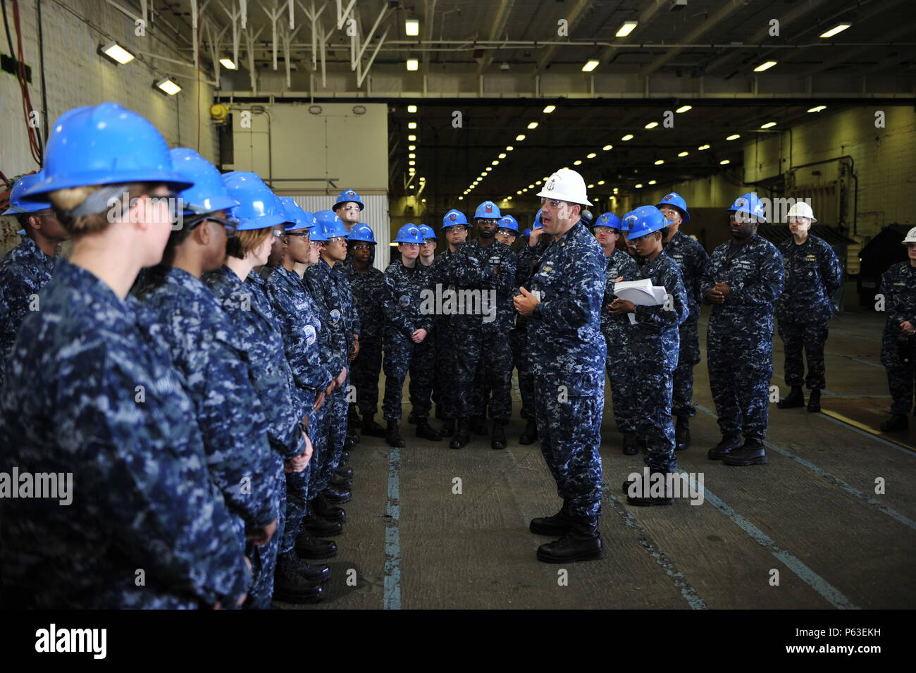 NEWPORT NEWS, Va. (Apr 19, 2016) -- Senior Chief Boatswain's Mate Edwin Bennett assigned to Pre-Commissioning Unit Gerald R. Ford (CVN 78) briefs sailors during departmental quarters in the ship's hangar bay. Ford is the first of a new class of aircraft carriers currently under construction by Huntington Ingalls industries Newport News Shipbuilding. (U.S. Navy photo by Mass Communication Specialist Seaman Apprentice Connor Loessin/Released) - Stock Image