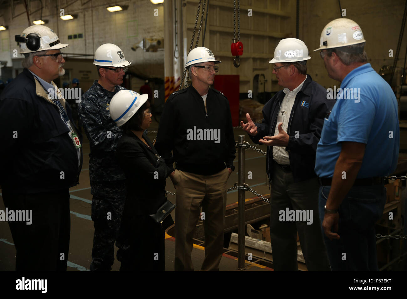NEWPORT NEWS, Va. (Apr 20, 2016) -- Rear Adm. Thomas Moore takes a tour of Pre-Commissioning Unit Gerald R. Ford (CVN 78) with super intendants of Huntington Ingalls Industries Newport News Shipbuilding (HIINNS). Ford is the first of a new class of aircraft carriers currently under construction by HIINNS. (U.S. Navy photo by Mass Communication Specialist Seaman Apprentice Connor Loessin/Released) (This image was altered for security purpose by blurring out security badges) - Stock Image
