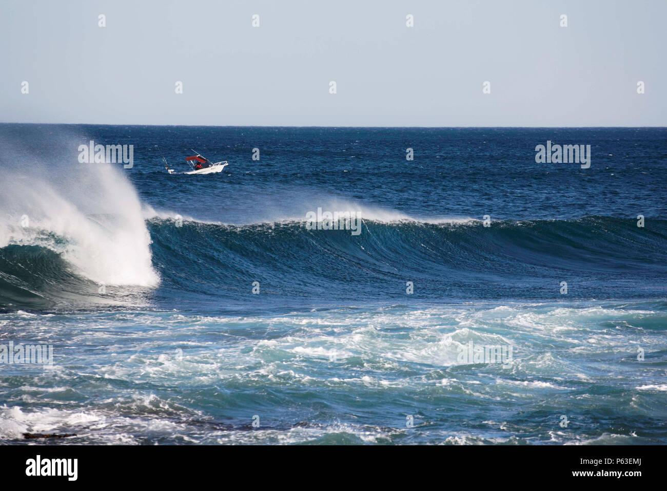 Small power boat and large breaking wave, Kalbarri  Western Australia - Stock Image