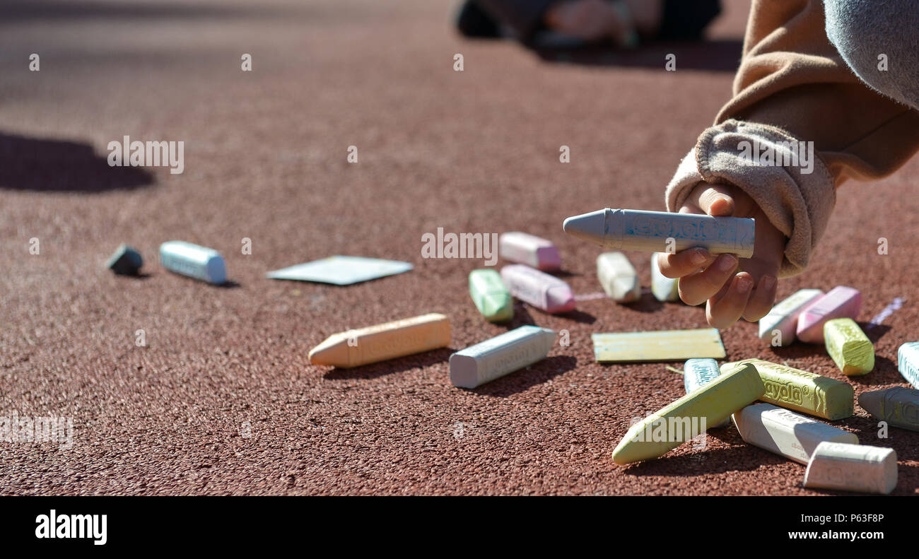 A child picks up a stick of chalk during a therapy session at Vogelweh Elementary School April 21, 2016, at Vogelweh Military Complex, Germany. Many children who had to leave Turkey and separate from their family serving there have been placed in new schools around the Kaiserslautern Military Community in Germany. While attending these new schools they undergo therapy to cope with their stresses and anxieties built up during the transition. - Stock Image