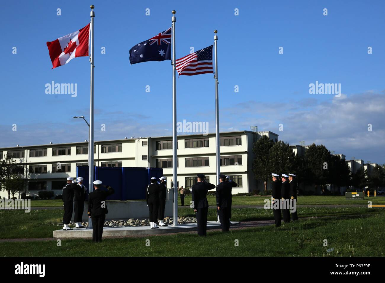 160425-N-DC740-042 OAK HARBOR, Wash. (April 25, 2016) Sailors from Naval Air Station Whidbey Island (NASWI) along with members of the Royal Australian Air Force (RAAF) and Royal Canadian Navy salute during a flagpole ceremony at NASWI. NASWI hosted the ceremony in honor of the joint cooperation between the U.S. Navy, RAAF and RCN. (U.S. Navy photo by Mass Communication Specialist 2nd Class John Hetherington/Released) - Stock Image